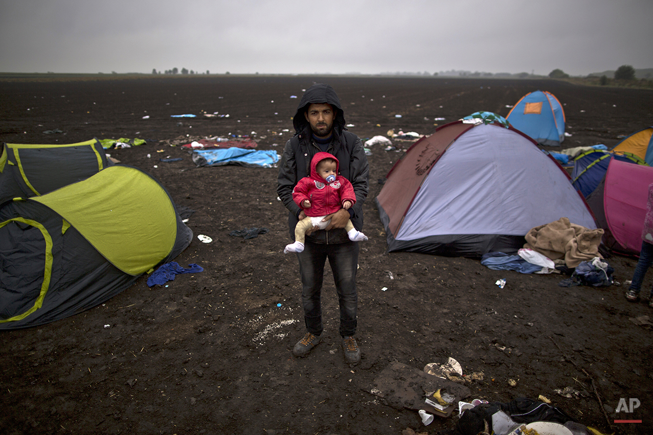 """In this photo taken on Friday, Sept. 11, 2015, Syrian refugee Waleed Mohammed, 30, who came from Aleppo, Syria, holds his 9-month-old son Omar while posing for a picture after they crossed the Serbian-Hungarian border near Roszke, southern Hungary. """"Whatever it takes I have one goal, a safe and better future for my wife and two children. The cold water didn't matter and the brutality of the police in Macedonia, I can see my wife and child traumatized but hopefully they will have a better future in Sweden,"""" he said. (AP Photo/Muhammed Muheisen)"""