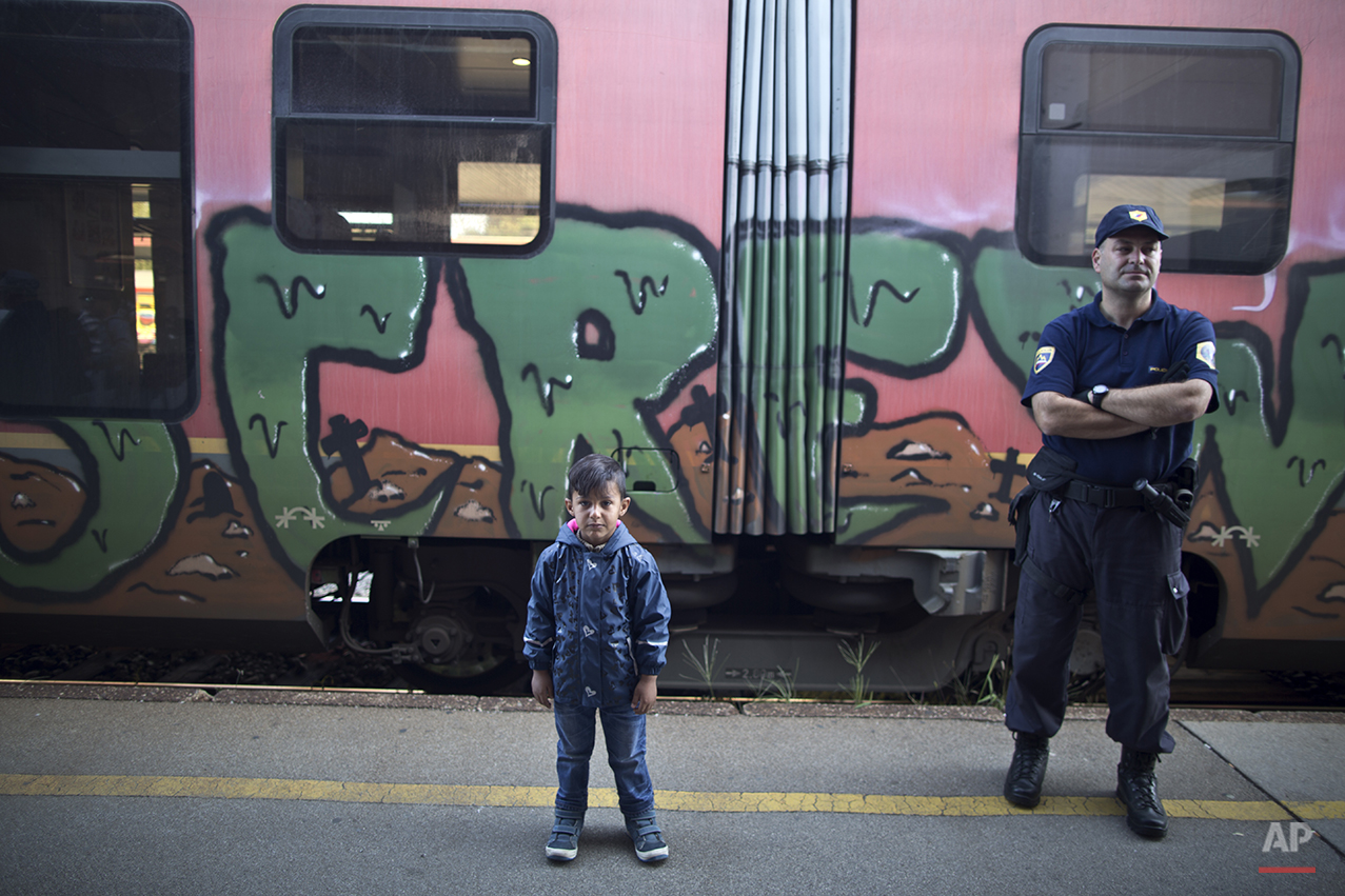 """In this photo taken on Monday, Sept. 21, 2015, Iraqi refugee Sajjad Hussein, 5, who came with parents from Basra, Iraq, poses for a picture while waiting to board a train in Celje, Slovenia. """"I am going with my family to Sweden, can't wait to arrive,"""" he said. (AP Photo/Muhammed Muheisen)"""