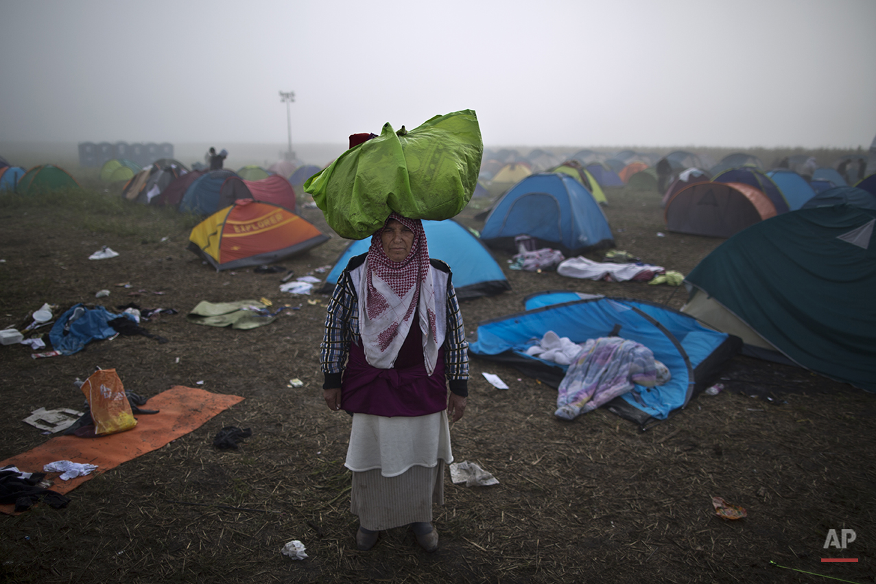 """In this photo taken on Saturday, Sept. 12, 2015, Syrian refugee Sabha Nasser, 62, who came from al-Hasaka, Syria, carries her belongings on her head as poses for a picture, after crossing the Serbian-Hungarian border near Roszke, southern Hungary. """"We had to flee our homes, the shelling is endless. I am old and I need peace. These last 15 days on the road were so humiliating and so miserable I just hope tomorrow will be better,"""" she said. (AP Photo/Muhammed Muheisen)"""