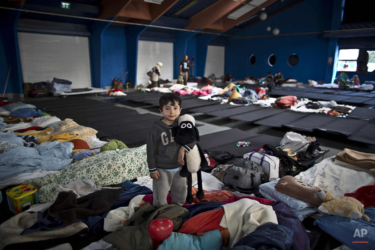 """In this photo taken on Tuesday, Sept. 22, 2015, Syrian refugee Osama Bakir, 5, who came with his parents from Aleppo, Syria, holds his toy while posing for a picture in a shelter near Graz, Austria. """"We are going to Germany,"""" he said. (AP Photo/Muhammed Muheisen)"""