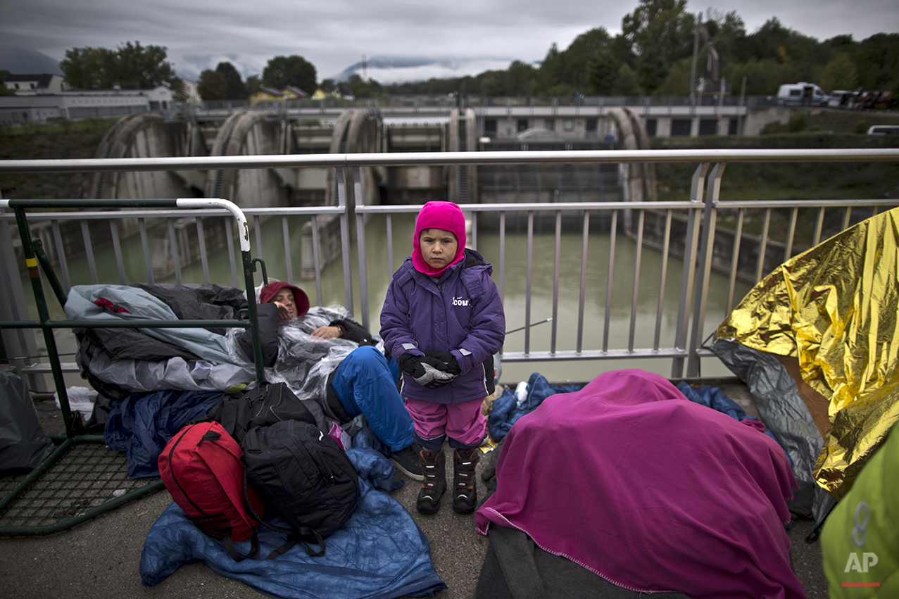 """In this photo taken on Thursday, Sept. 24, 2015, Syrian refugee Abdulwahab Alabdullah, 5, who came with his family from Aleppo, Syria, poses for a picture while waiting on a bridge after they spent the night waiting for their registration and transport by German police to a refugee shelter in Freilassing, Germany. """"I am so cold waiting with my father and mother and younger brother from two days in this bridge,"""" he said. (AP Photo/Muhammed Muheisen)"""