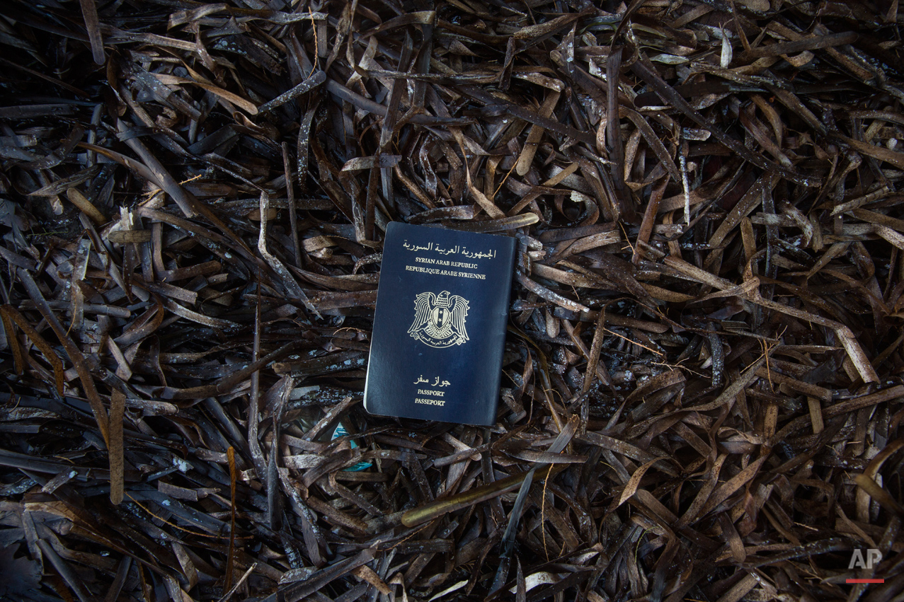 In this Thursday, Oct. 8, 2015 photo a Syrian passport found on the road that runs along the north of the Greek island of Lesbos is placed to be portrayed on a beach next to the town of Skala Sikaminias, on the northeastern Greek island of Lesbos. (AP Photo/Santi Palacios)