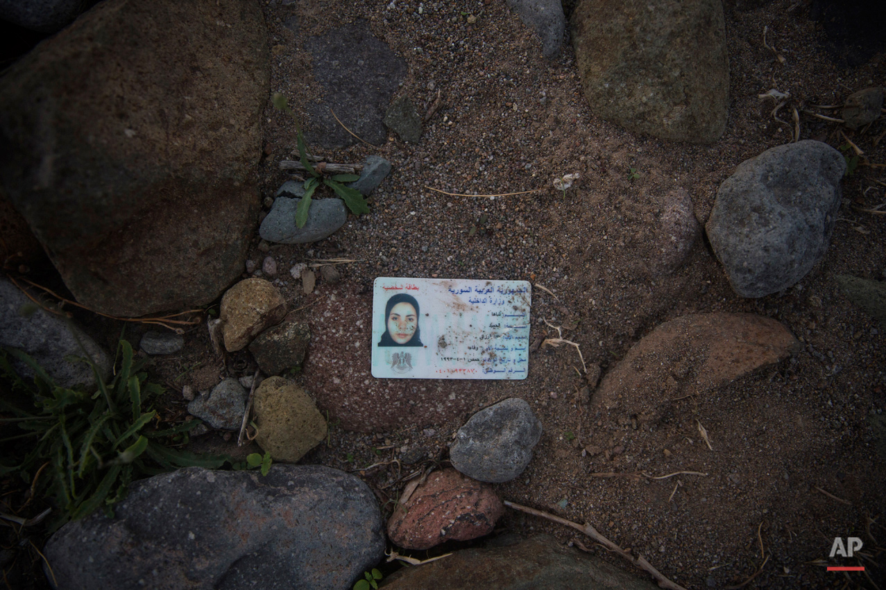 In this Sunday, Oct. 4, 2015 photo, the national identity card of a Syrian woman remains left behind on a beach next to the town of Molyvos, on the northeastern Greek island of Lesbos. The migrants arrive by the hundreds on the beaches of the Greek island of Lesbos. And in their eagerness to move on, they leave behind belongings they carried with them.  (AP Photo/Santi Palacios)