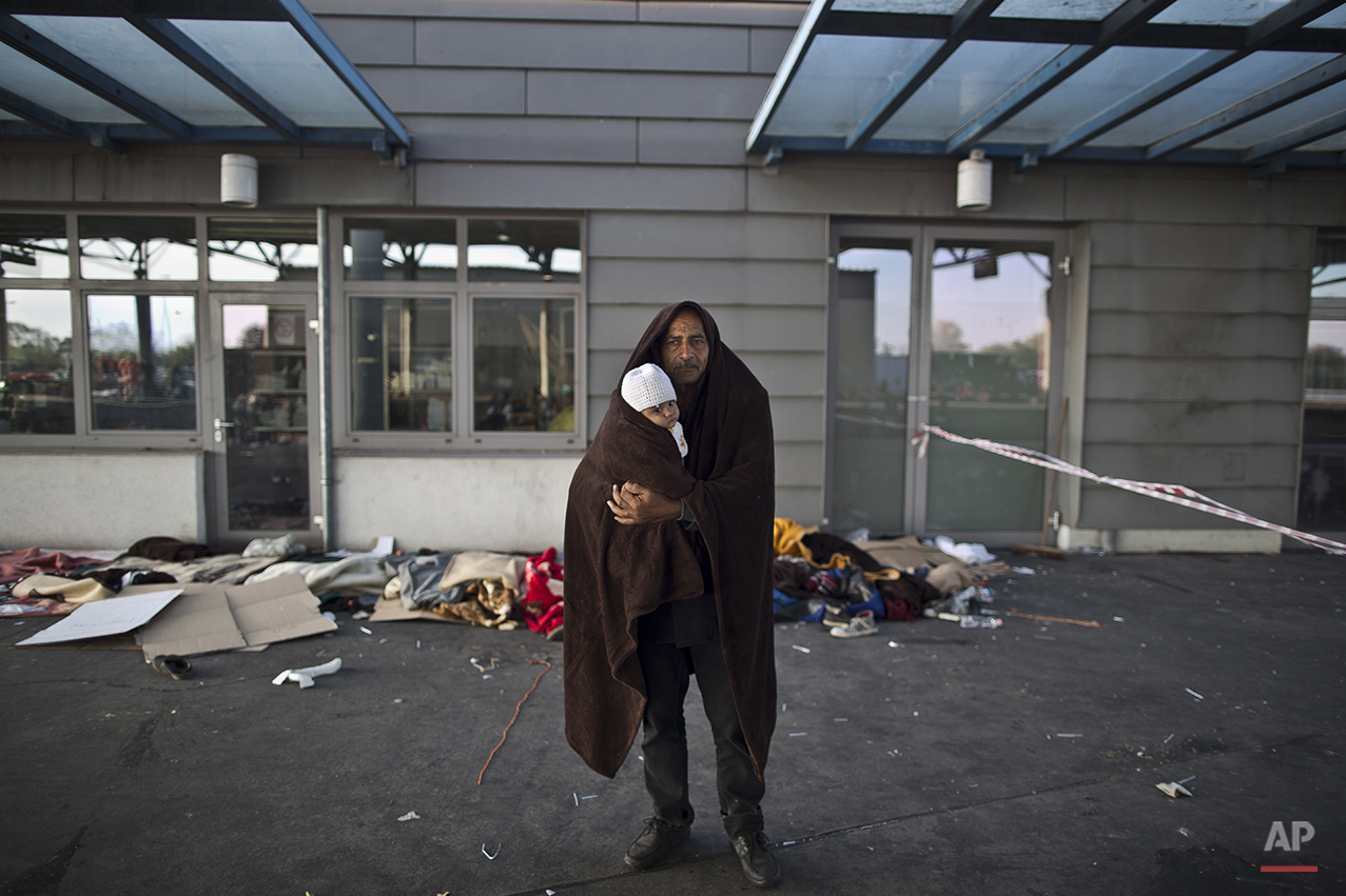 """In this photo taken on Wednesday, Sept. 23, 2015, Syrian refugee Jamal Almasri, 54, who came from Damascus, Syria, wraps himself and his granddaughter with a shawl to shelter from the morning cold as he poses for a picture, after spending the night at a collection point in the truck parking lot of the former border station on the Austrian side of the Hungarian-Austrian border near Nickelsdorf, Austria. Almasri said, """"We met death, we just want to have a life, any life with a rooftop and a shelter. Our lives are over, what matters is the children."""" (AP Photo/Muhammed Muheisen)"""