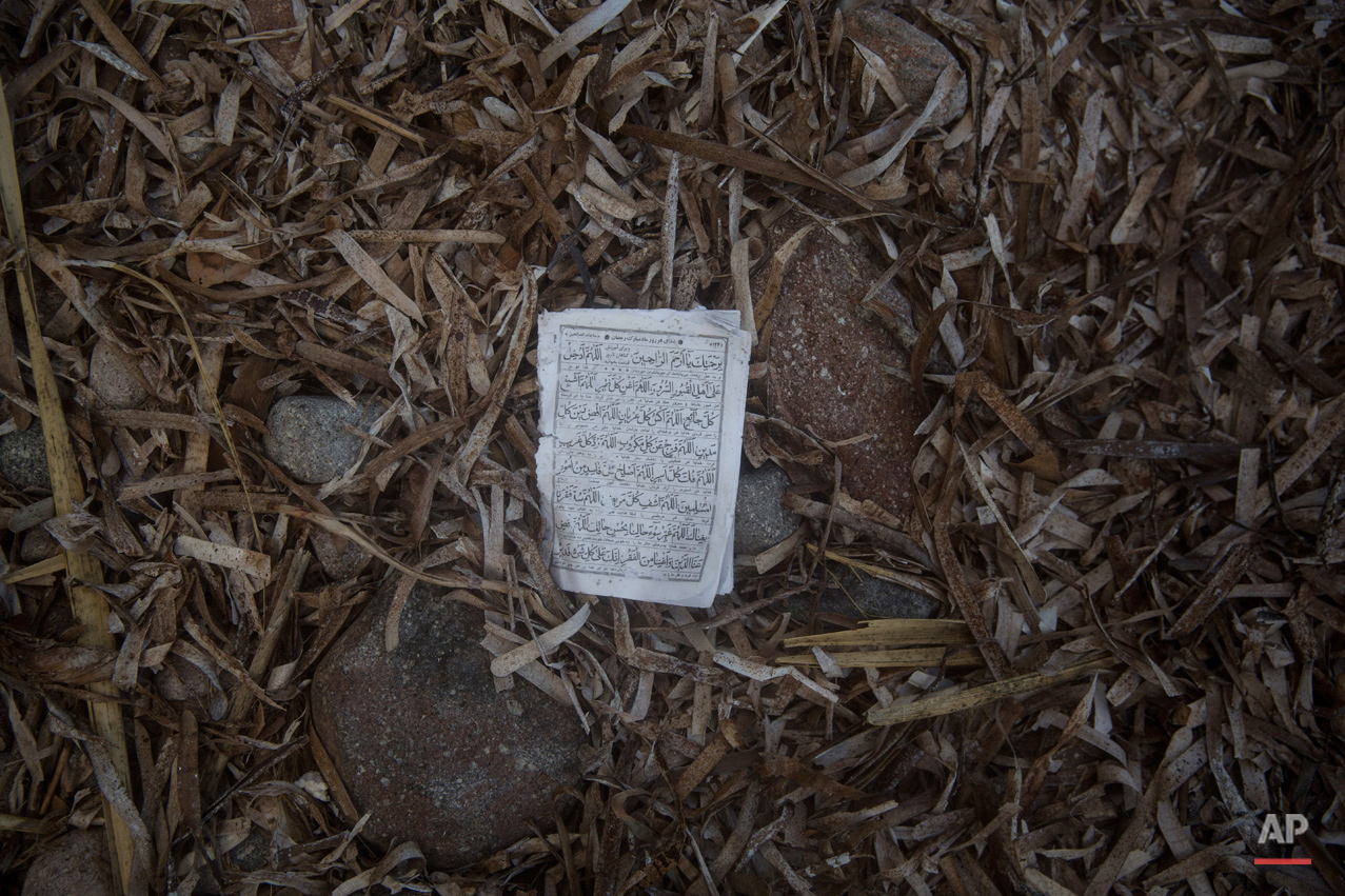 In this Friday, Oct. 2, 2015 photo, a page from a Quran,  the holy book of Muslims, lies on the beach in the Greek island of Lesbos. The migrants arrive by the hundreds on the beaches of the Greek island of Lesbos. And in their eagerness to move on, they leave behind belongings they carried with them.  (AP Photo/Santi Palacios)