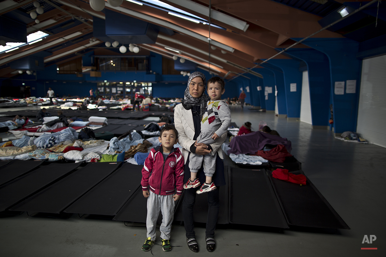 """In this photo taken on Tuesday, Sept. 22, 2015, Iranian Hamideh Salehi, 38, center and her children Ali, 6, left, and Hussein, 2, who came from Mashhad, Iran, pose for a picture in a shelter where they took refuge near Graz, Austria. """"Weeks of walking was very difficult for my children, the cold in the nights, we were hungry and thirsty, we walked for so long and I had to carry my children. I am happy I am here at this shelter in Austria, I dream of freedom and a good education for my kids that's all I want,"""" Salehi said. (AP Photo/Muhammed Muheisen)"""