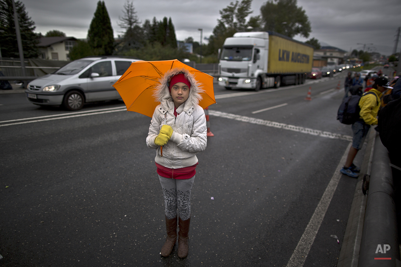 """In this photo taken on Thursday, Sept. 24, 2015, Afghan refugee Fatima Rezai, 10, who came with her parents from Mazar-i Sharif, Afghanistan, poses for a picture while waiting on a bridge after spending the night waiting for their registration and transport by German police to a refugee shelter in Freilassing, Germany. """"Life in Afghanistan is so scary especially for girls, I was so afraid in this trip was so difficult and long walking, I am hoping to become a doctor in Germany and help people,"""" she said. (AP Photo/Muhammed Muheisen)"""