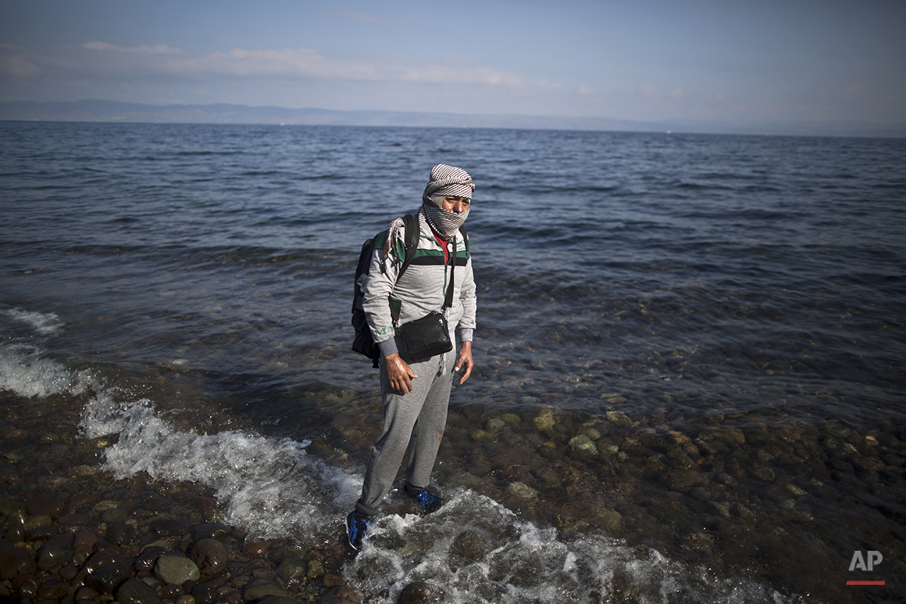 """In this photo taken on Saturday, Oct. 3, 2015, Syrian refugee Ala'aldeen Mohammed, 25, who was injured in 2013 in a government bombing that burnt his upper body and face, who came from Aleppo, Syria, poses for a picture shortly after arriving on a dinghy from the Turkish coast to the northeastern Greek island of Lesbos. """"In Germany, they can cure the burns from my injury following a government airstrike in 2013 that I have all over my upper body,"""" he said. (AP Photo/Muhammed Muheisen)"""