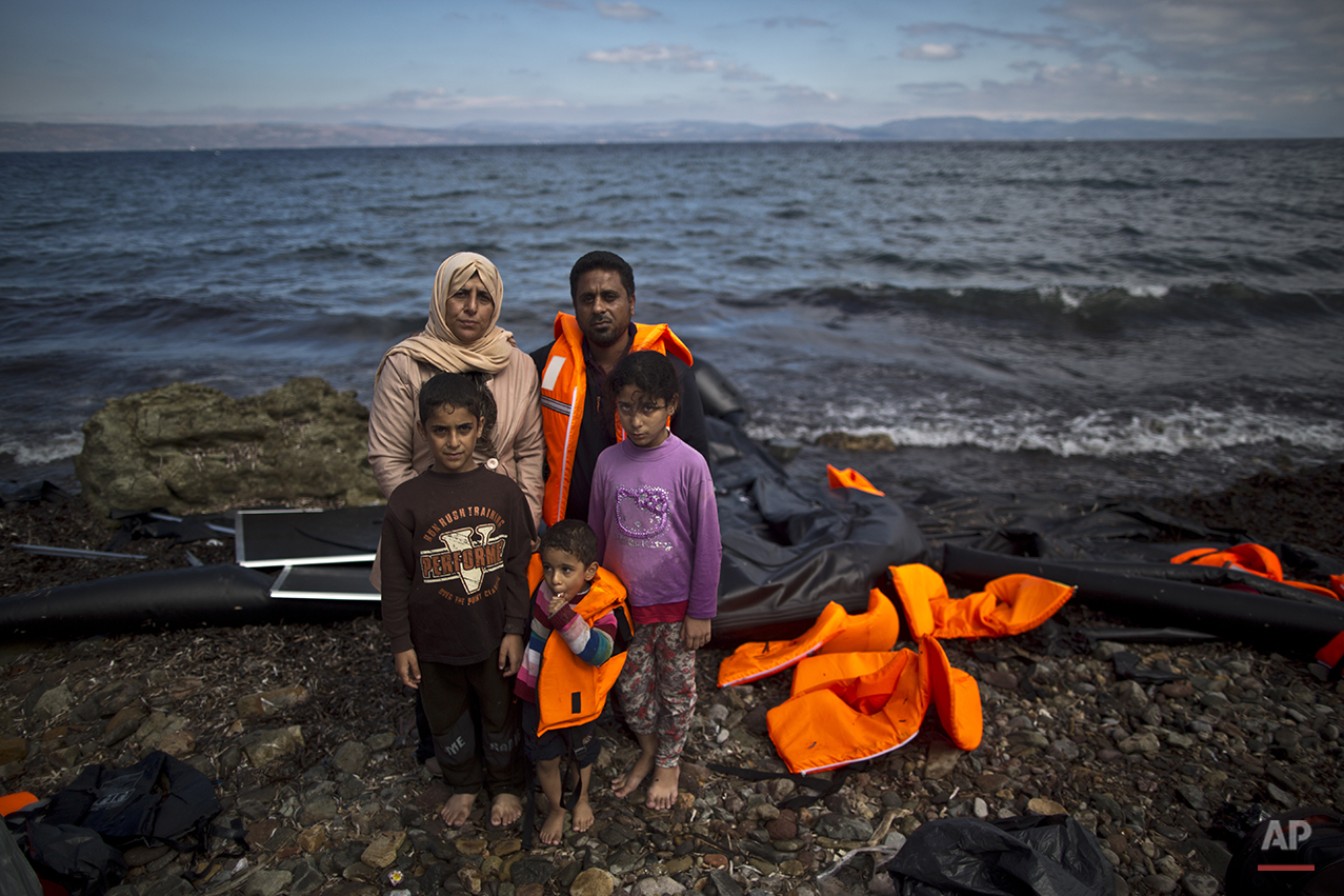 """In this photo taken on Thursday, Oct. 1, 2015, Iraqi refugee Mohammed Sadoun, 39, and his wife Suhad, 35, who came from Mosul, Iraq, pose for a picture with their children from right, Abdulrahman, 9, Abdullah, 3, and Hadeel, 11, shortly after arriving on a dinghy from the Turkish coast to the northeastern Greek island of Lesbos. """"We had to run from Islamic State, IS, death will reach us all if we don't. I wish to reach Germany where humanity exists, and my children will grow up with a bright future,"""" Mohammed Sadoun said. (AP Photo/Muhammed Muheisen)"""