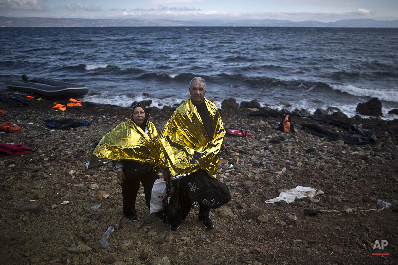 """In this photo taken on Friday, Oct. 2, 2015, Syrian refugee Ali Shaheen, 62, and his wife Abeer, 52, who came from the countryside of Damascus, Syria, pose for a picture shortly after arriving on a dinghy from the Turkish coast to the northeastern Greek island of Lesbos. """"Me and my wife are old and we can't walk, we were mistreated in Turkey, we are so tired,"""" Ali said. (AP Photo/Muhammed Muheisen)"""