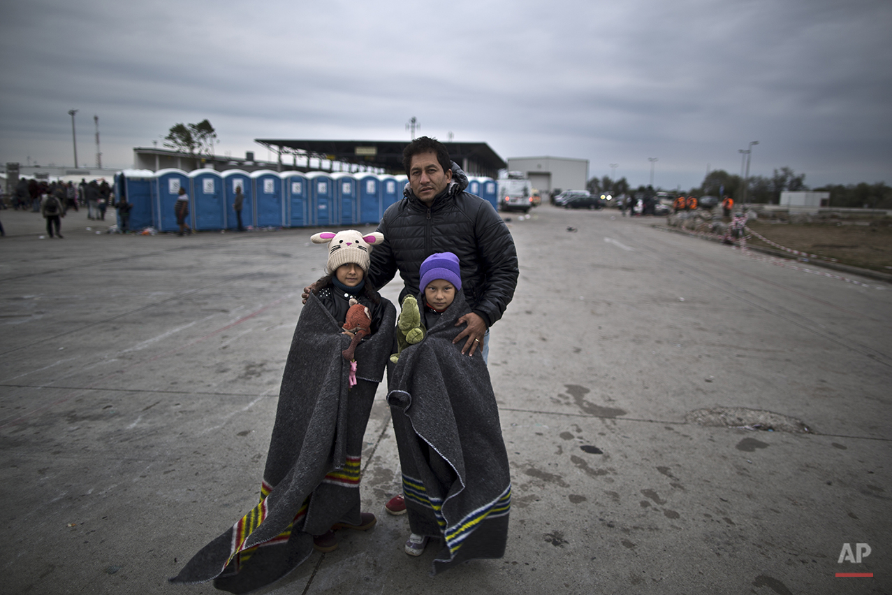 """In this photo taken on Friday, Sept. 25, 2015, Afghan refugee Abdullah Hussein, 39, and his daughters Satara, left and Rukhsara, who came from Mazar-i Sharif, Afghanistan, pose for a picture after spending the night at a collection point in the truck parking lot of the former border station on the Austrian side of the Hungarian-Austrian border near Nickelsdorf, Austria. """"I don't know which country I am going to or will end in, I just want my children to have a future. In Afghanistan we are in war for the last four decades, but no one paid us attention, we live a tough life and no one cares for us and we are stuck, I just want to provide a good future to my children, after this trip there is no turning back to Afghanistan,"""" Hussein said (AP Photo/Muhammed Muheisen)"""