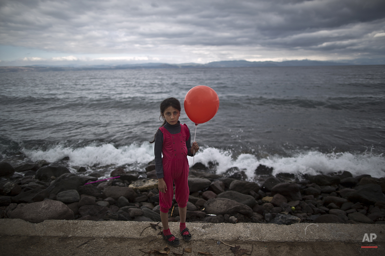 """In this photo taken on Friday, Oct. 2, 2015, Syrian refugee Raghad Faleh, 8, who came with her family from Idlib, Syria, poses for a picture while holding a balloon given to her by volunteers, a few hours after she and her family arrived on a dinghy from the Turkish coast to the northeastern Greek island of Lesbos. """"My feet are killing me from pain, I walked a lot,"""" Faleh said. (AP Photo/Muhammed Muheisen)"""
