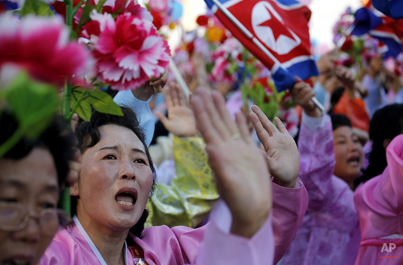 North Koreans wave decorative flowers and some break into tears as they parade past their leader Kim Jong Un, in Pyongyang, North Korea, Saturday, Oct. 10, 2015. North Korean leader Kim Jong Un declared Saturday that his country was ready to stand up to any threat posed by the United States as he spoke at a lavish military parade to mark the 70th anniversary of the North's ruling party and trumpet his third-generation leadership.(AP Photo/Wong Maye-E)