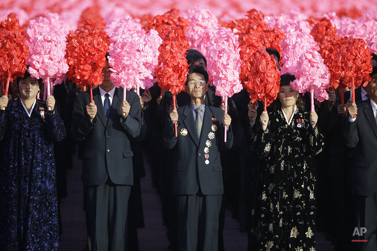 North Koreans hold decorative flowers during a military parade in Pyongyang, North Korea, Saturday, Oct. 10, 2015. North Korean leader Kim Jong Un declared Saturday that his country was ready to stand up to any threat posed by the United States as he spoke at a lavish military parade to mark the 70th anniversary of the North's ruling party and trumpet his third-generation leadership. (AP Photo/Wong Maye-E)