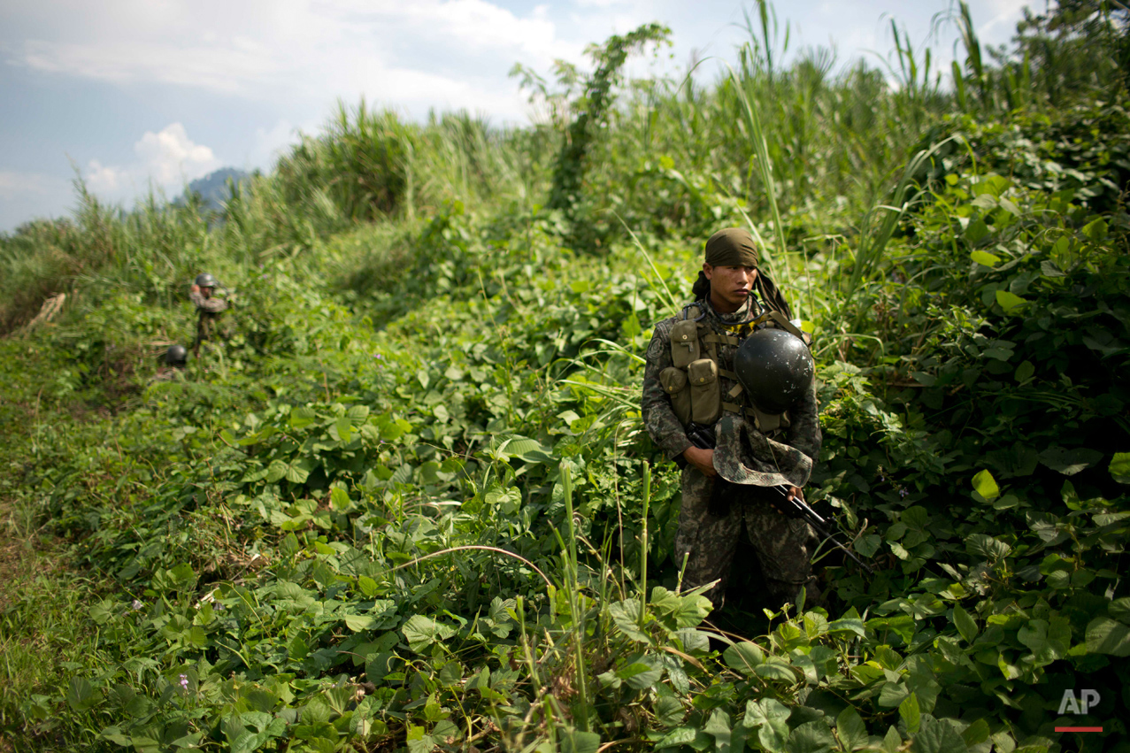 In this Sept. 19, 2014 photo, a soldier stands guard during the destruction of a clandestine airstrip in the Valley of the Apurimac, Ene and Mantaro River Valleys, or VRAEM, the world's No. 1 coca-growing region in Ayacucho, Peru. Peruvian and Bolivian officials have agreed during a meeting in La Paz to share information in real time on cross-border drug flights. They did not, however, divulge details. (AP Photo/Rodrigo Abd)