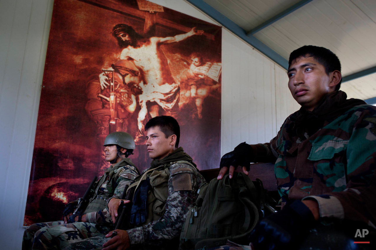 In this Sept. 19, 2014 photo, soldiers sit, back dropped by an image of Jesus Christ embracing a praying soldier, inside a building at the Mazamari counternarcotics base in the Valley of the Ene and Apurimac and Mantaro River Valleys, or VRAEM, the world's No. 1 coca-growing region, in Junin, Peru. An average of about  4-5 small planes daily fly into Peru from Bolivia, picking up about 300 kilos each of coca paste worth about a third of a million dollars in Bolivia. (AP Photo/Rodrigo Abd)