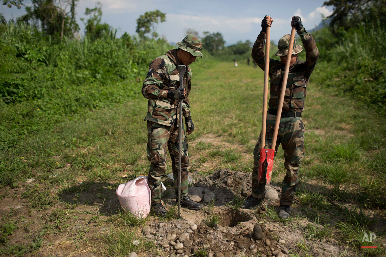 In this Sept. 19, 2014 photo, counternarcotics officers make hole for placing explosives during the destruction of a clandestine airstrip in the Apurimac, Ene and Mantaro River Valleys, or VRAEM, the world's No. 1 coca-growing region, in Ayacucho, Peru. The dynamiting of craters by Peruvian security forces into clandestine airstrips in the VRAEM cuts into profits but hardly discourages cocaine traffickers who net tens of thousands of dollars with each flight. (AP Photo/Rodrigo Abd)