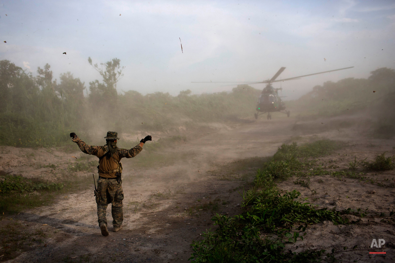 In this Sept. 19, 2014 photo, a Peruvian counternarcotics agent signals to a military helicopter a landing area on a clandestine airstrip in the Valley of the Apurimac, Ene and Mantaro River Valleys, or VRAEM, the world's No. 1 coca-growing region in Junin, Peru. Security forces destroyed in the last two weeks more than 50 clandestine airstrips for drug planes in the biggest offensive that seeks to combat the intense drug airlift to Bolivia. According to authorities, two of the landing strips cratered in this latest operation have each been repaired four times this year, the 500-meter airstrips are fixed overnight. (AP Photo/Rodrigo Abd)