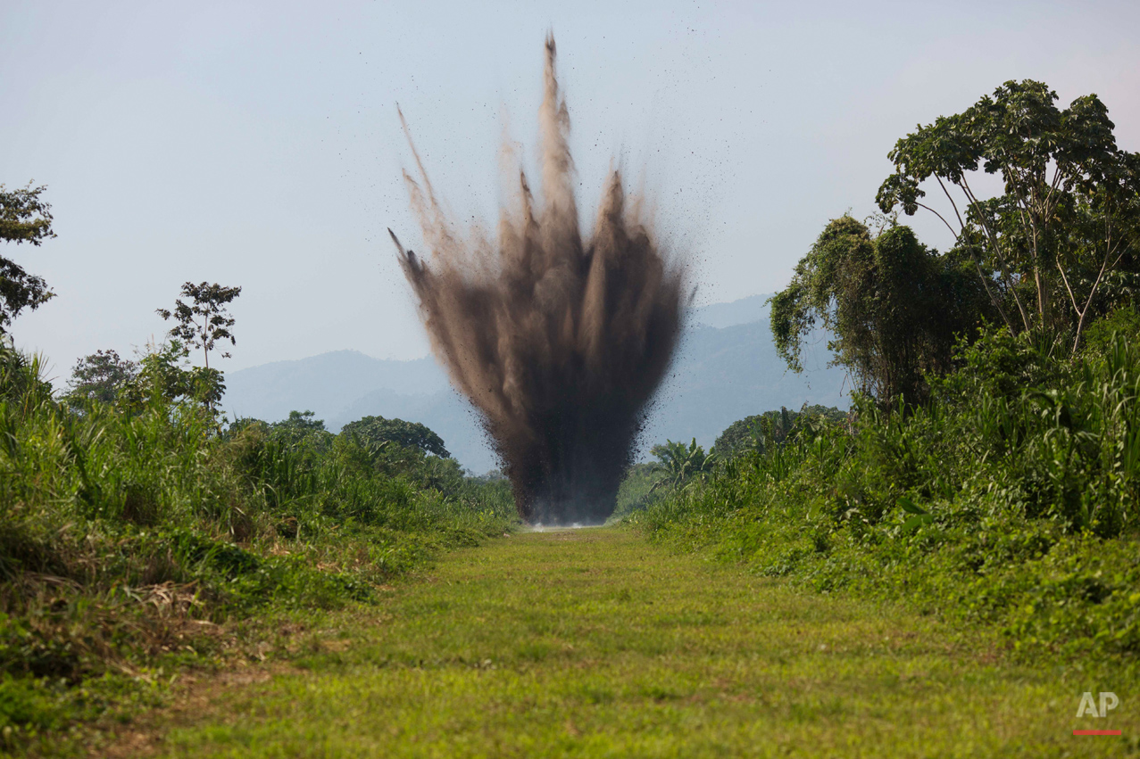 AP10ThingsToSee - In this Sept. 19, 2014 photo, explosives are detonated by Peruvian counternarcotics forces on a part of a clandestine grassy airstrip in the Apurimac, Ene and Mantaro River Valleys, or VRAEM, the world's No. 1 coca-growing region, in Ayacucho, Peru. The dynamiting of craters by Peruvian security forces into clandestine airstrips cuts into profits but hardly discourages cocaine traffickers who net tens of thousands of dollars with each flight flown from these airstrips. (AP Photo/Rodrigo Abd)