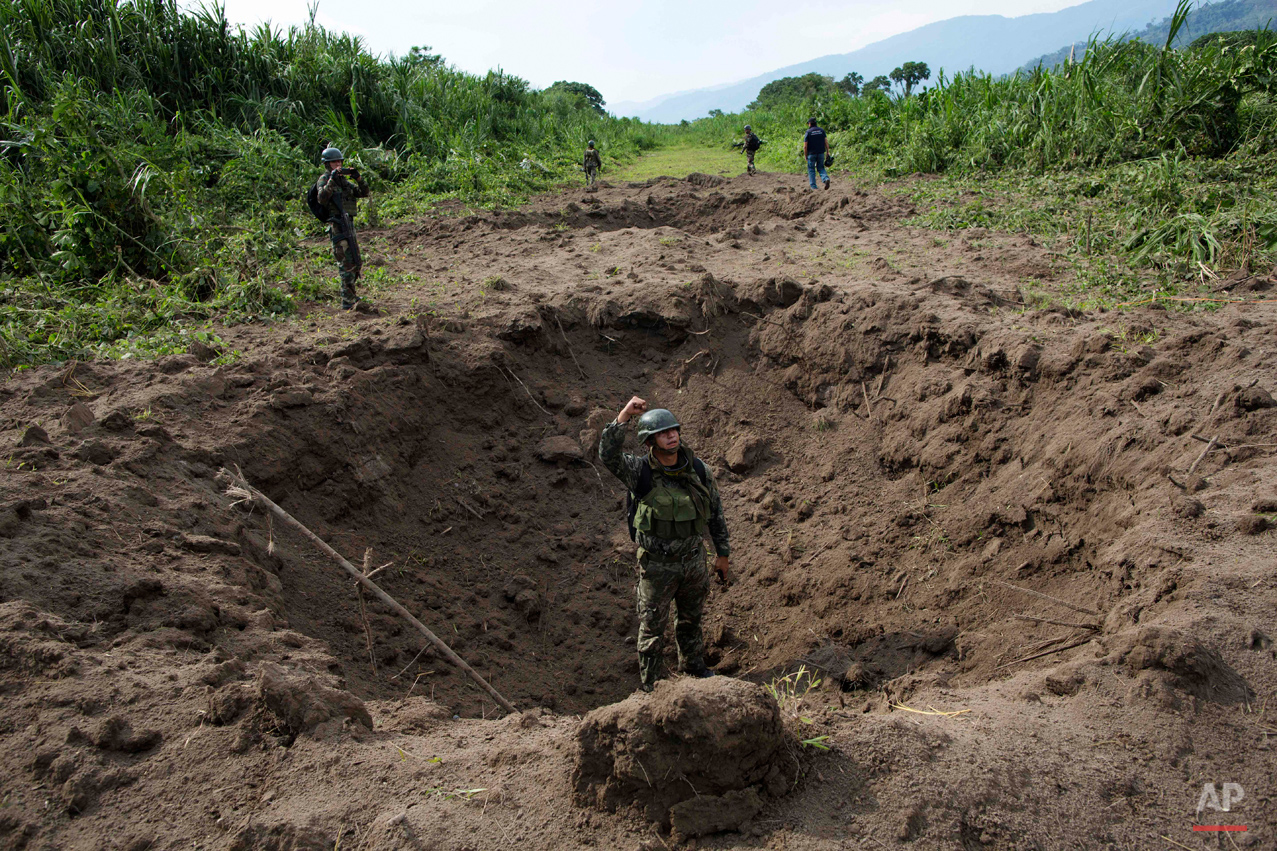 In this Friday, Sept. 19, 2014 photo, a soldier signals to his commander while standing inside a crater created by explosives planted by Peruvian counternarcotics forces on part of a clandestine grassy airstrip, in the Valley of the Apurimac, Ene and Mantaro River Valleys, or VRAEM, the world's No. 1 coca-growing region in Ayacucho, Peru. According to official data, Peru has blown craters into 132 clandestine airfields this year, up from 110 last year. (AP Photo/Rodrigo Abd)