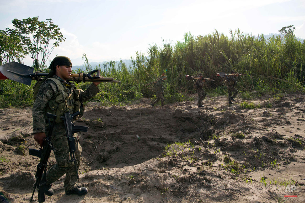 In this Sept. 19, 2014 photo, soldiers walk around a crater created by explosives planted by Peruvian counternarcotics forces on part of a clandestine grassy airstrip, located in the Apurimac, Ene and Mantaro River Valleys, or VRAEM, the world's No. 1 coca-growing region, in Ayacucho, Peru. According to authorities traffickers pay local villagers up to $100 each to fill the holes blasted into the landing strips that dot the floodplain. (AP Photo/Rodrigo Abd)