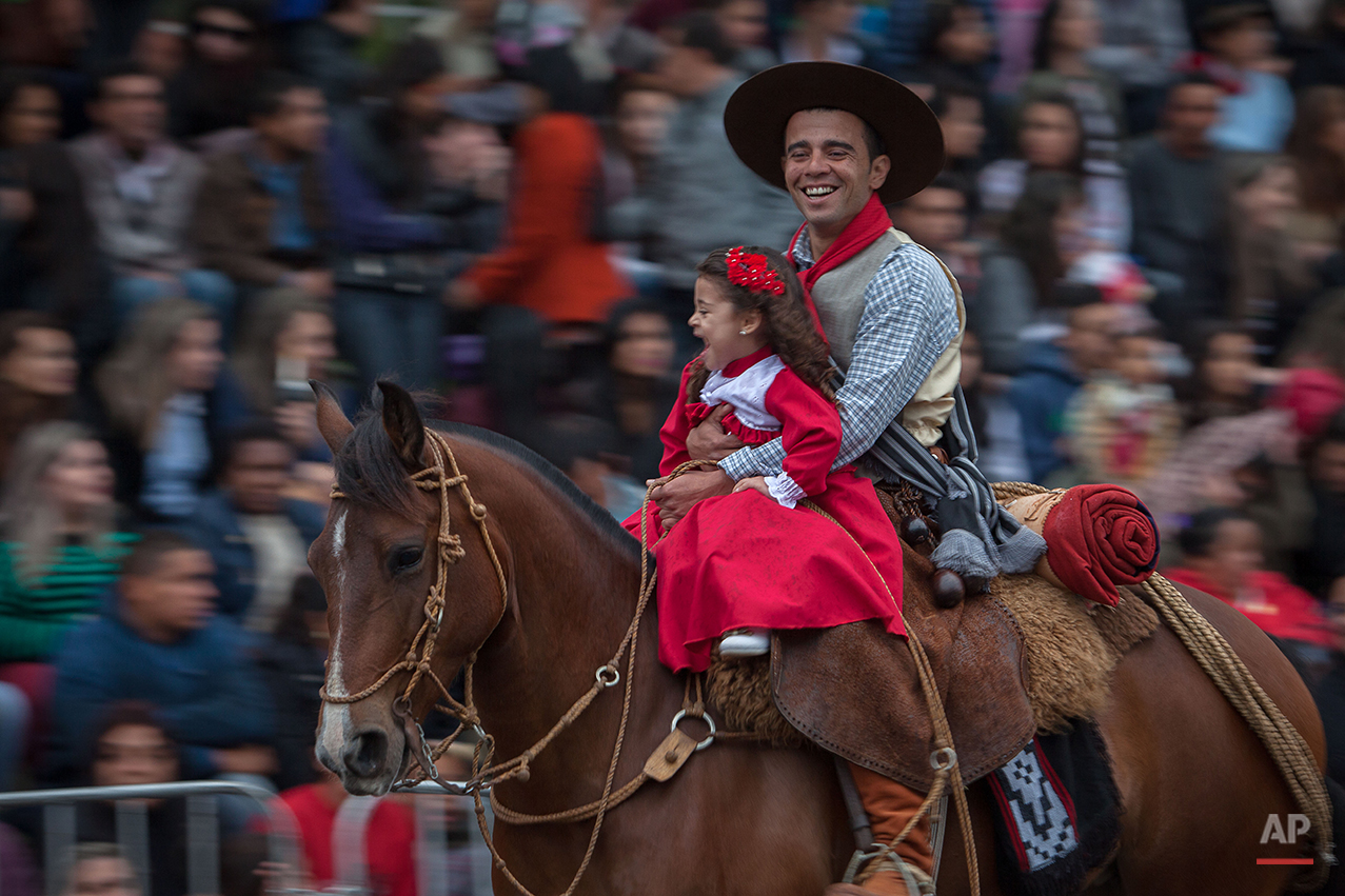 """In this Sept. 20, 2015 photo, a father with his daughter smile during a parade at the Semana Farroupilha or """"Ragamuffin"""" week, in Alegrete municipality, Rio Grande do Sul state, Brazil. Some of the Brazilian cowboys ride with little girls wearing old-fashioned dresses. They parade before crowds in southern Rio Grande do Sul state, which fancies itself as practically a separate nation, with its rugged rural traditions and Germanic roots. (AP Photo/Eraldo Peres)"""