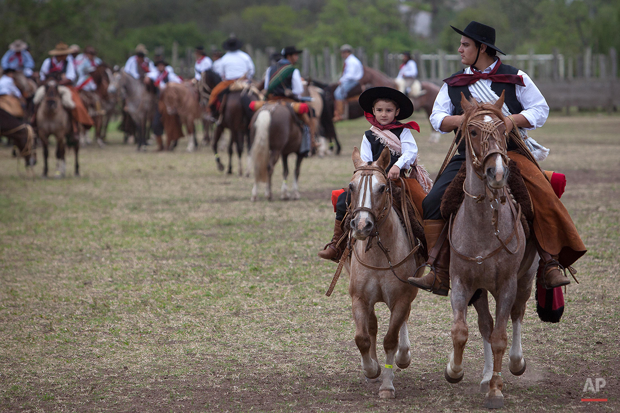 """In this Sept. 20, 2015 photo, a boy and his father prepare to participate in the parade of Semana Farroupilha or """"Ragamuffin"""" week, in Alegrete municipality, Rio Grande do Sul state, Brazil. Each September, the locals keep their cowboy cultural alive with two weeks of traditional dances, lectures, book readings and camping out under the stars. (AP Photo/Eraldo Peres)"""