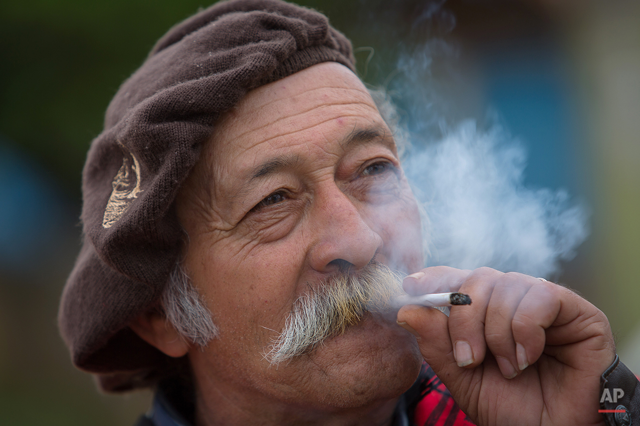 """In this Sept. 19, 2015 photo, gaucho Jose Newton Franca Silveira, 66, smokes a cigarrette during the Semana Farroupilha or """"Ragamuffin"""" week, in Alegrete municipality, Rio Grande do Sul state, Brazil. Each September, the locals keep their cowboy cultural alive with two weeks of traditional dances, lectures, book readings and camping out under the stars. (AP Photo/Eraldo Peres)"""