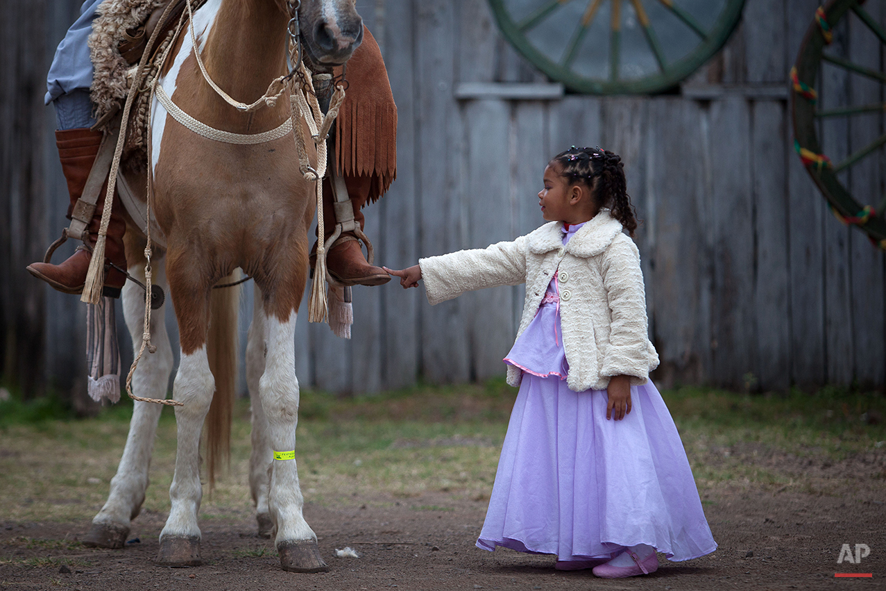 """In this Sept. 20, 2015 photo, girl Alessandra Fortes de Lima, 6, touches the boot of her father Adimir Goncalves de Lima, 49, before a parade during the Semana Farroupilha or """"Ragamuffin"""" week, in Alegrete municipality, Rio Grande do Sul state, Brazil. Some of the Brazilian cowboys ride with little girls wearing old-fashioned dresses. They parade before crowds in southern Rio Grande do Sul state, which fancies itself as practically a separate nation, with its rugged rural traditions and Germanic roots. (AP Photo/Eraldo Peres)"""