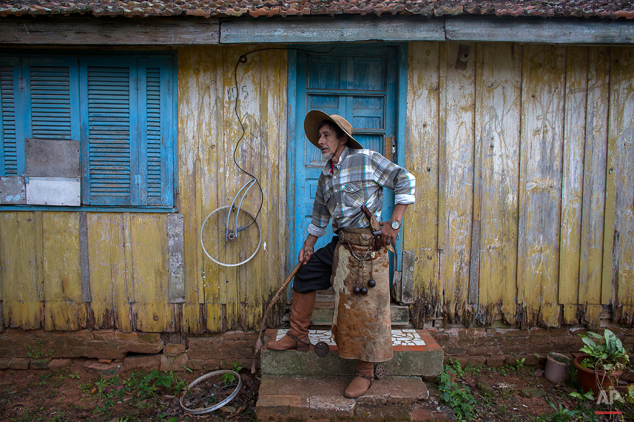 """In this Sept. 19, 2015 photo, gaucho Leo Moura, poses for a photo in front his home during the Semana Farroupilha or """"Ragamuffin"""" week, in Alegretemunicipality, Rio Grande do Sul state, Brazil. Each September, the locals keep their cowboy cultural alive with two weeks of traditional dances, lectures, book readings and camping out under the stars. (AP Photo/Eraldo Peres)"""