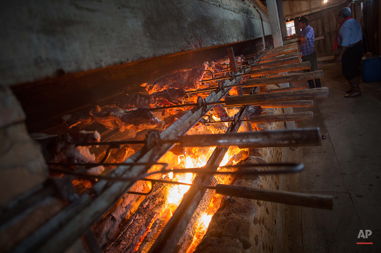 """In this Sept. 19, 2015 photo, gauchos prepare a barbecue or """"churrasco"""" for launch during Semana Farroupilha or """"Ragamuffin"""" week, in Alegrete municipality, Rio Grande do Sul state, Brazil. It's a different world here, about 700 miles southwest of the Brazilian megalopolis of Sao Paulo. Today, revolution is no longer on the table _ instead it's the endless rows of barbecued beef. The region is known for having Brazil's best steaks, ribs, sausages and other carnivorous delights, all slow roasted over massive pit of flames. (AP Photo/Eraldo Peres)"""