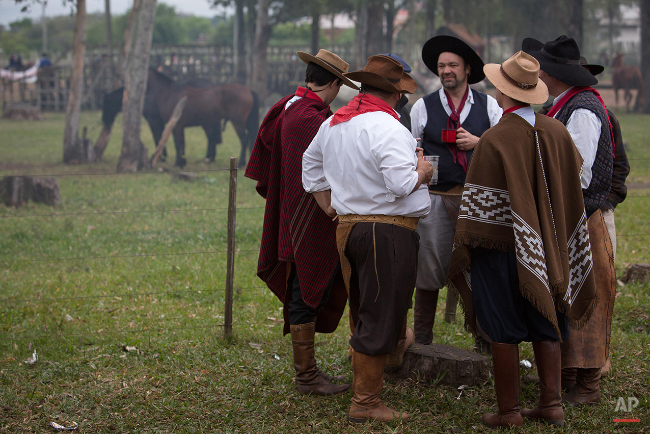 """In this Sept. 20, 2015 photo, gauchos wearing traditional clothes gather before the Semana Farroupilha or """"Ragamuffin"""" week in Alegrete municipality, Rio Grande do Sul state, Brazil. Celebrated every September, the regional revolt is known as the """"Ragamuffin Revolution"""" because the poor fighters wore raggedy clothing in an insurgency that took a decade to put down. (AP Photo/Eraldo Peres)"""