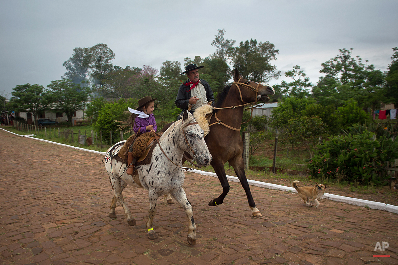 """In this Sept. 19, 2015 photo, a girl and her grandfather ride their horses before a parade during the Semana Farroupilha or """"Ragamuffin"""" week, in Alegrete municipality, Rio Grande do Sul state, Brazil. Some of the Brazilian cowboys ride with little girls wearing old-fashioned dresses. They parade before crowds in southern Rio Grande do Sul state, which fancies itself as practically a separate nation, with its rugged rural traditions and Germanic roots. (AP Photo/Eraldo Peres)"""