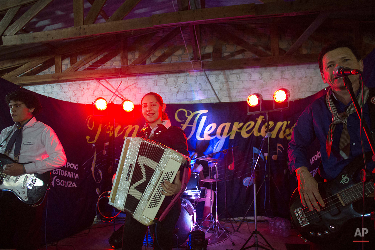 """In this Sept. 19, 2015 photo, a band play music during Semana Farroupilha or """"Ragamuffin"""" week celebrations, in Alegrete municipality, Rio Grande do Sul state, Brazil. During the celebration, cowboy culture is kept alive with traditional dances to accordion music, lectures, book readings and camping out under the stars. (AP Photo/Eraldo Peres)"""