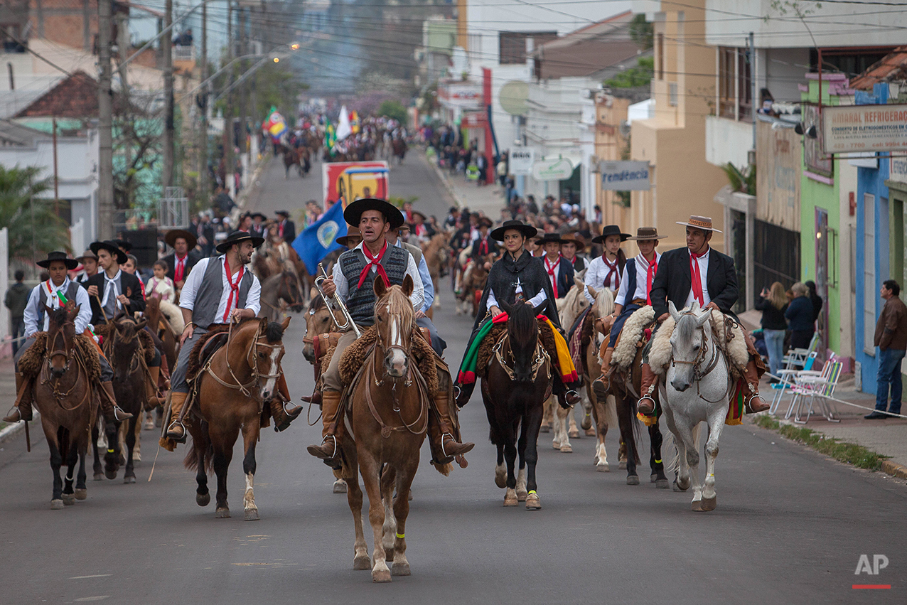 """In this Sept. 20, 2015 photo, gauchos parade during the Semana Farroupilha or """"Ragamuffin"""" week, downtown in Alegrete municipality, Rio Grande do Sul state, Brazil. Wearing traditional broad-brimmed hats and red neckerchiefs, their trousers tucked into soft, leather boots, the South American gauchos trot on handsome horses down the street of the small southern community. (AP Photo/Eraldo Peres)"""