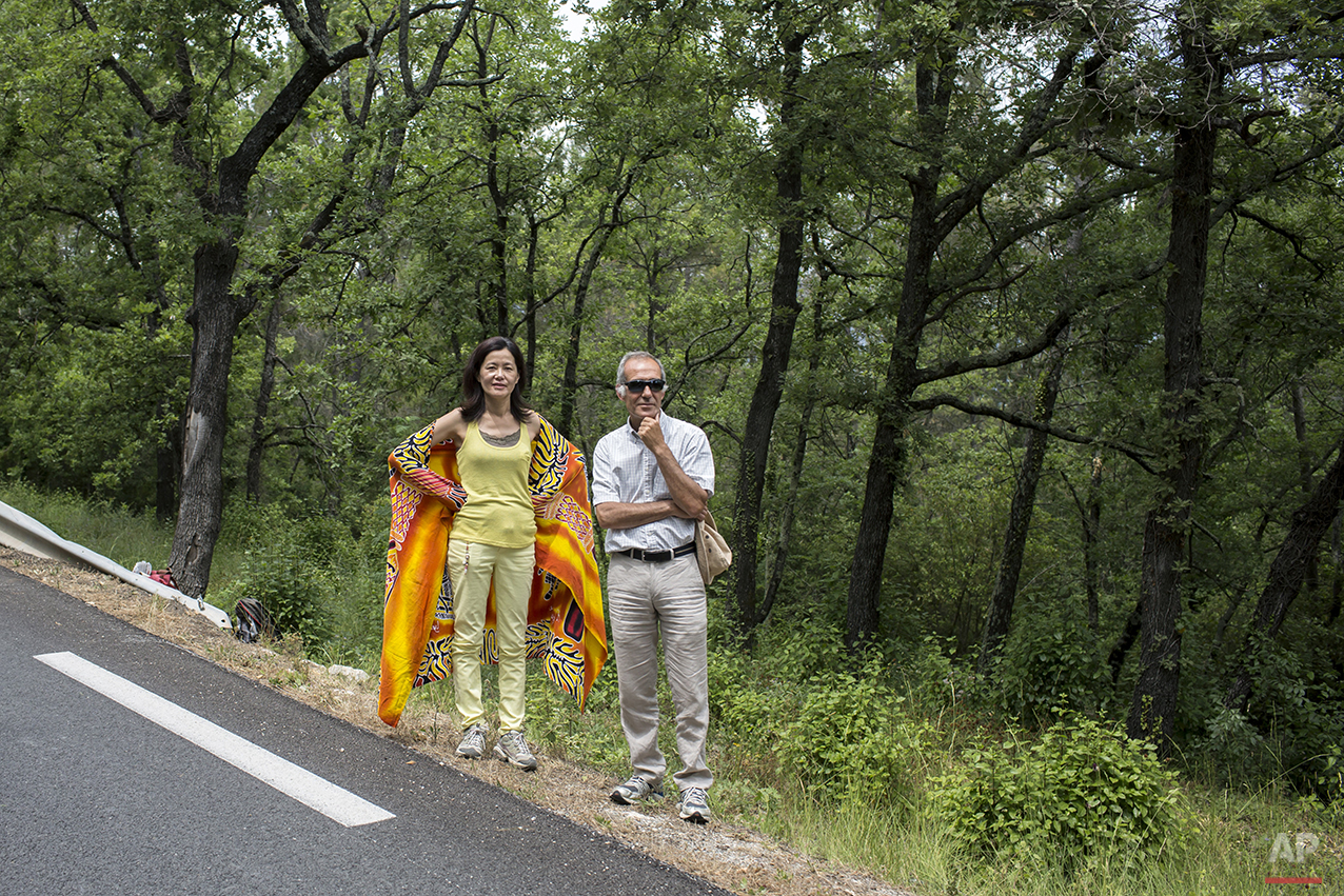 A man and a woman stand on the side of the road as they wait for the fifth stage of the 100th edition of the Tour de France, between Cagnes-sur-Mer and Marseille, France, Wednesday, July 3, 2013. (AP Photo/Laurent Cipriani)
