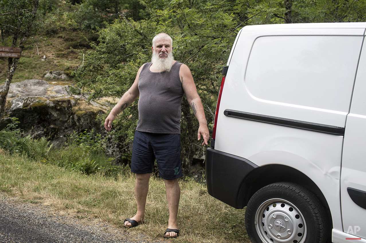 A man stands by his vehicle as he waits for cyclists to pass during the twelfth stage of the 102nd edition of the Tour de France, between Lannemezan and Plateau de Beille, France, Thursday, July 16. (AP Photo/Laurent Cipriani)