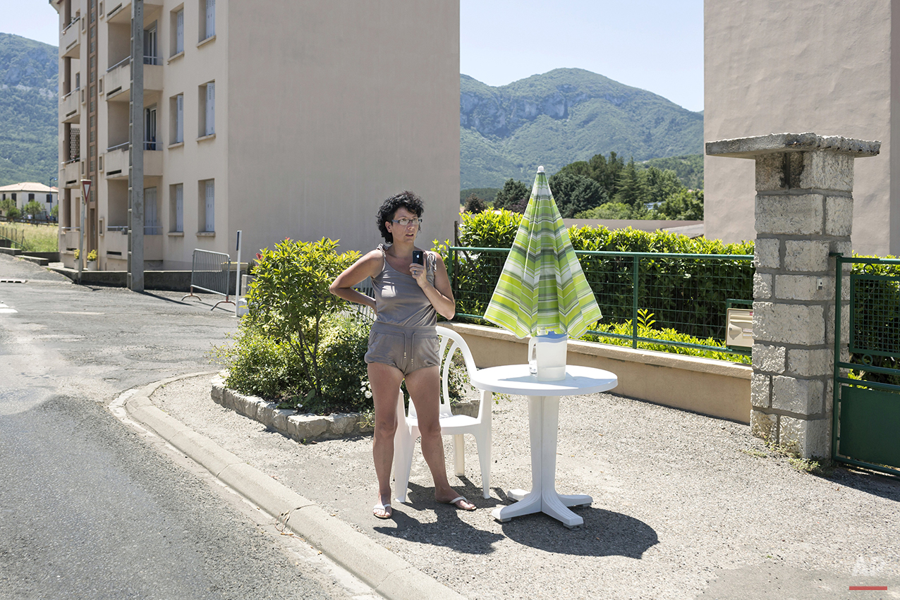 A woman stands on the side of the road to watch the eighth stage of the 100th edition of the Tour de France, between Castres and Ax 3 Domaines, France, Saturday, July 6, 2013. (AP Photo/Laurent Cipriani)