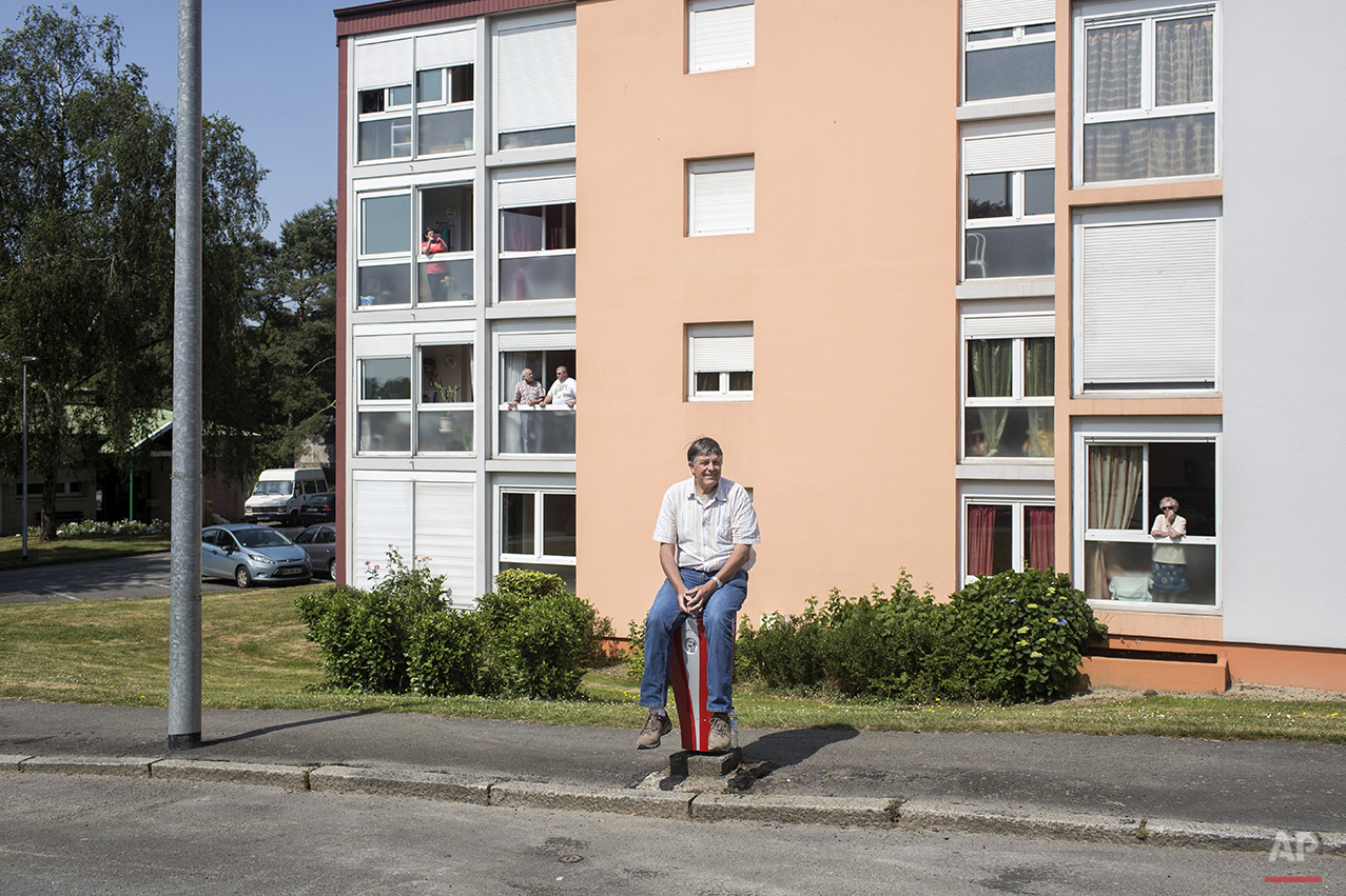 A man sits on a bollard on the side of the road as others stand in the windows of apartments as they wait for the arrival of the twelfth stage of the 100th edition of the Tour de France, between Fougeres and Tours, France, Thursday, July 11, 2013. (AP Photo/Laurent Cipriani)