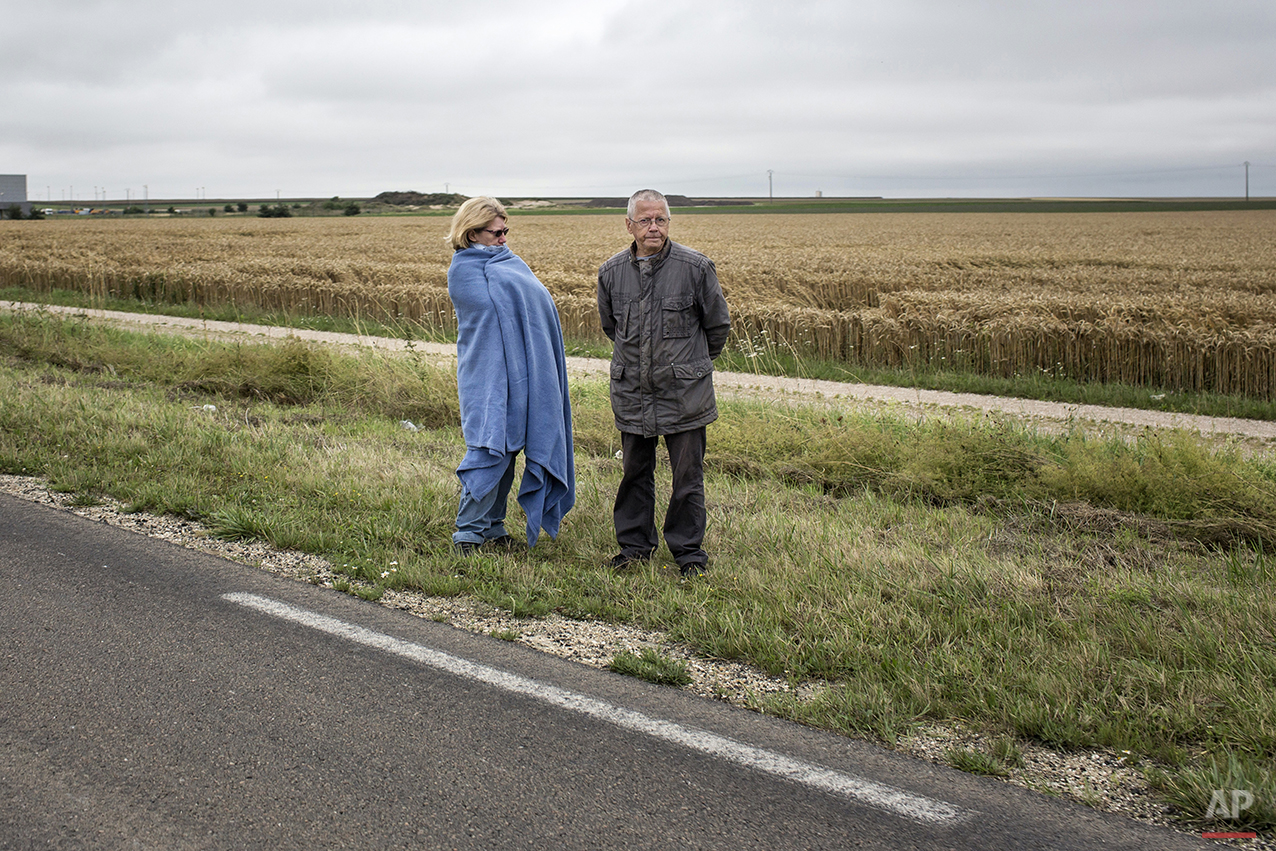 A man and a woman stand on the side of the road waiting for the arrival of competitors during the seventh stage of the 101st edition of the Tour de France, between Epernay and Nancy, France, Friday, July 11, 2014. (AP Photo/Laurent Cipriani)