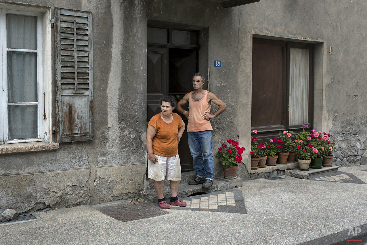 A couple stand outside their home as they wait for the pack to pass during the nineteenth stage of the 100th edition of the Tour de France, between Bourg-d'Oisans and Le Grand-Bornand, France, Friday, July 19, 2013. (AP Photo/Laurent Cipriani)