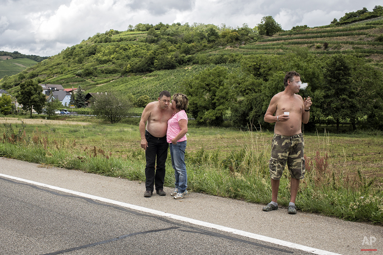 People wait for the arrival of cycle racers during the tenth stage of the 101st edition of the Tour de France, between Mulhouse and La Planche des Belles Filles, France, Monday, July 14, 2014. (AP Photo/Laurent Cipriani)