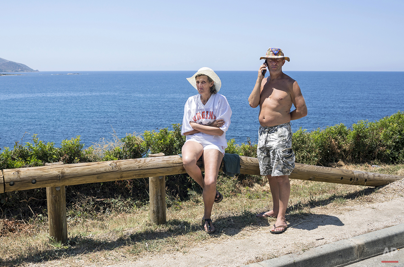 A man and a woman stand on the side of the road to watch the third stage of the 100th edition of the Tour de France, between Ajaccio and Calvi, France, Monday, July 1st, 2013. (AP Photo/Laurent Cipriani)