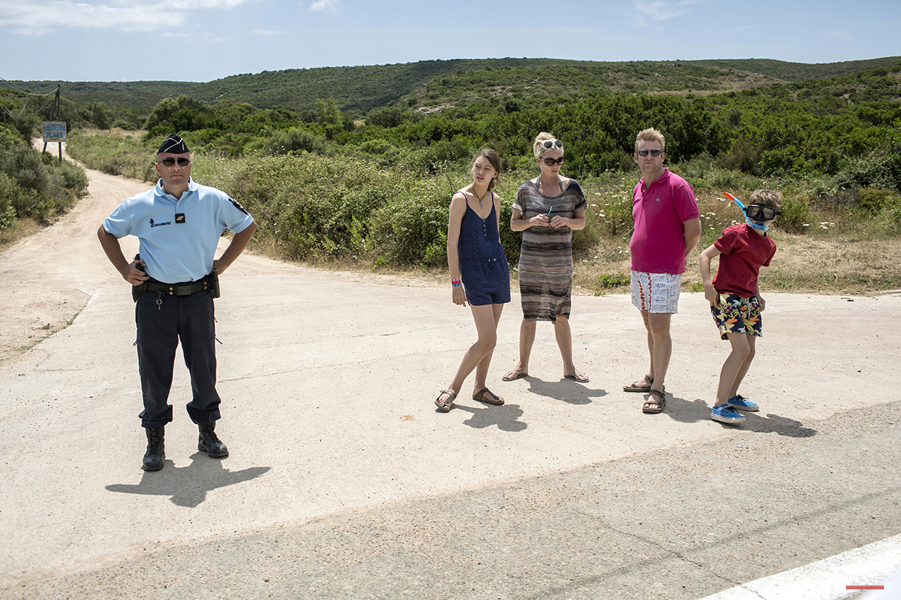Spectators stand next to a Gendarme as they gather to watch the the first stage of the 100th edition of the Tour de France, between Porto-Vecchio and Bastia, France, Saturday, June 29, 2013. (AP Photo/Laurent Cipriani)
