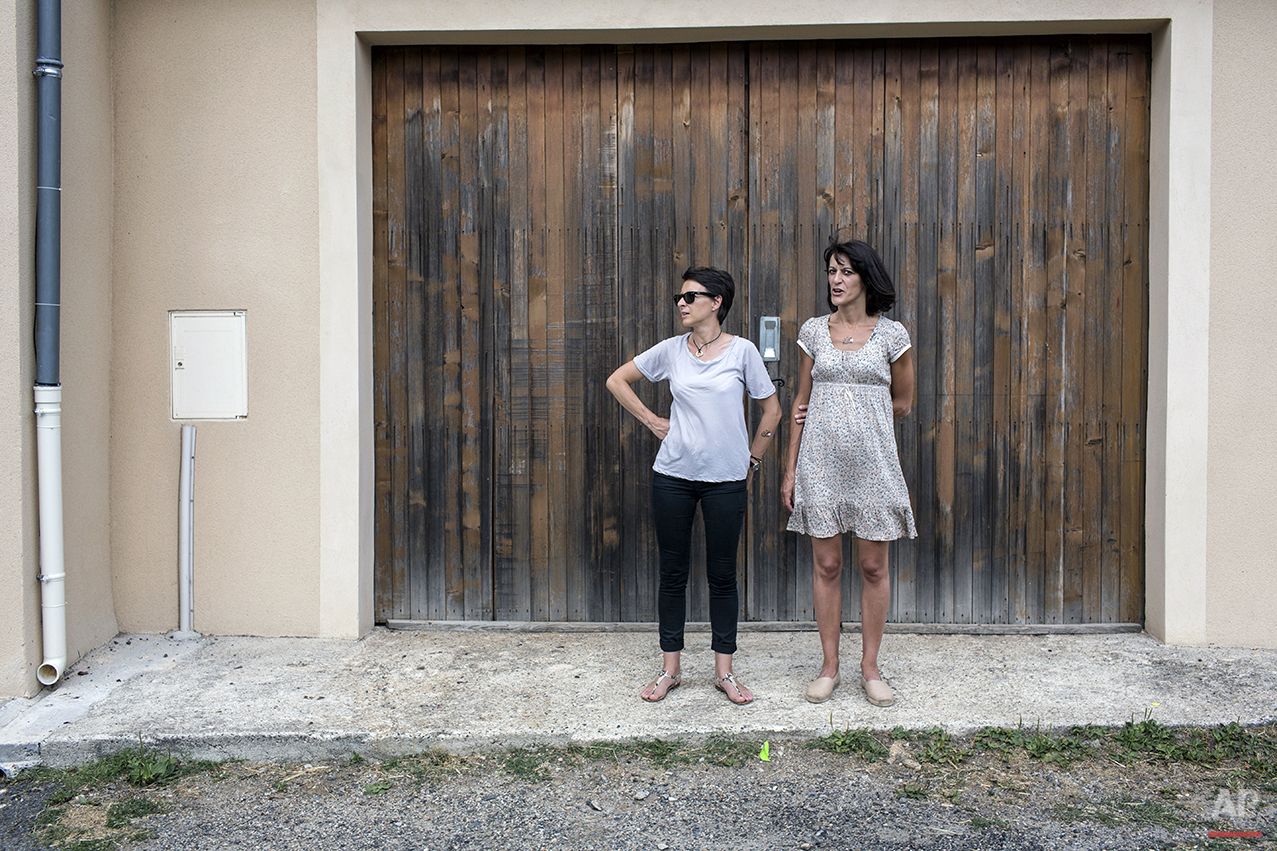 Two women stand outside a garage as they wait for the arrival of cycle racers during the fifteenth stage of the 102nd edition of the Tour de France, between Mende and Valence, France, Sunday, July 19, 2015. (AP Photo/Laurent Cipriani)