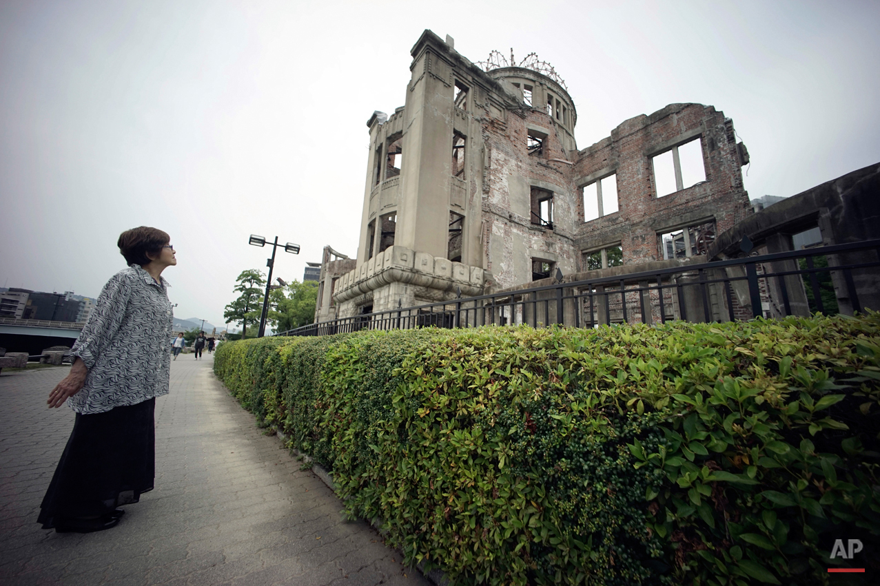 In this July 3, 2015 photo, Kimie Mihara, a survivor of the 1945 atomic bombing, looks at the Atomic Bomb Dome, as it is known today in Hiroshima, Hiroshima Prefecture, southern Japan. Built in 1915, the dome building was a rare example of Western architecture in Hiroshima at the time. Czech architect Jan Letzel designed it to be a city landmark and an exhibition hall for industrial and cultural promotion. Mihara was a worker at a government office in the dome building in 1945. (AP Photo/Eugene Hoshiko)