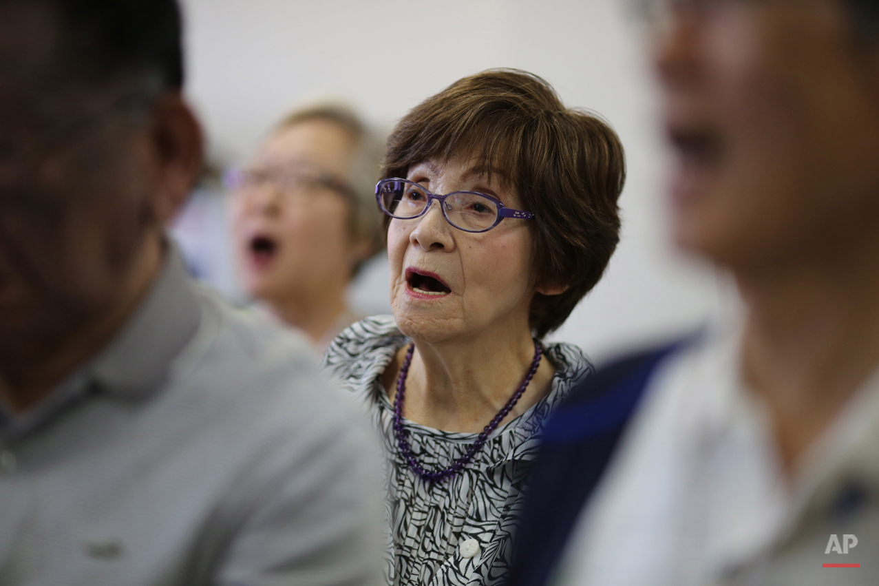 In this July 3, 2015 photo, Kimie Mihara, center, a survivor of the 1945 atomic bombing, participates a chorus at a community center in Hiroshima, Hiroshima Prefecture, southern Japan. On the morning of Aug. 6, 1945, the Atomic Bomb Dome, as it is known today, was her office. She was running late to work. Thatís the only reason sheís still alive. (AP Photo/Eugene Hoshiko)