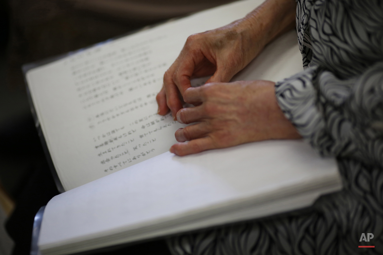 In this July 3, 2015 photo, Kimie Mihara, a survivor of the 1945 atomic bombing, participates in a chorus at a community center in Hiroshima, Hiroshima Prefecture, southern Japan. On the morning of Aug. 6, 1945, the Atomic Bomb Dome, as it is known today, was her office. She was running late to work. Thatís the only reason sheís still alive. (AP Photo/Eugene Hoshiko)