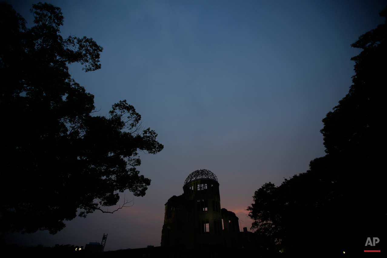 In this July 3, 2015 photo, the Atomic Bomb Dome, as it is known today is seen at dusk in Hiroshima, Hiroshima Prefecture, southern Japan. In its postwar rebuilding, Hiroshima decided to conserve the dome as it was in 1961, leaving it as an icon of devastation in a city where such scars were quickly becoming invisible. The building was registered as a UNESCO World Heritage site in 1996 to call for a non-nuclear world and world peace. (AP Photo/Eugene Hoshiko)