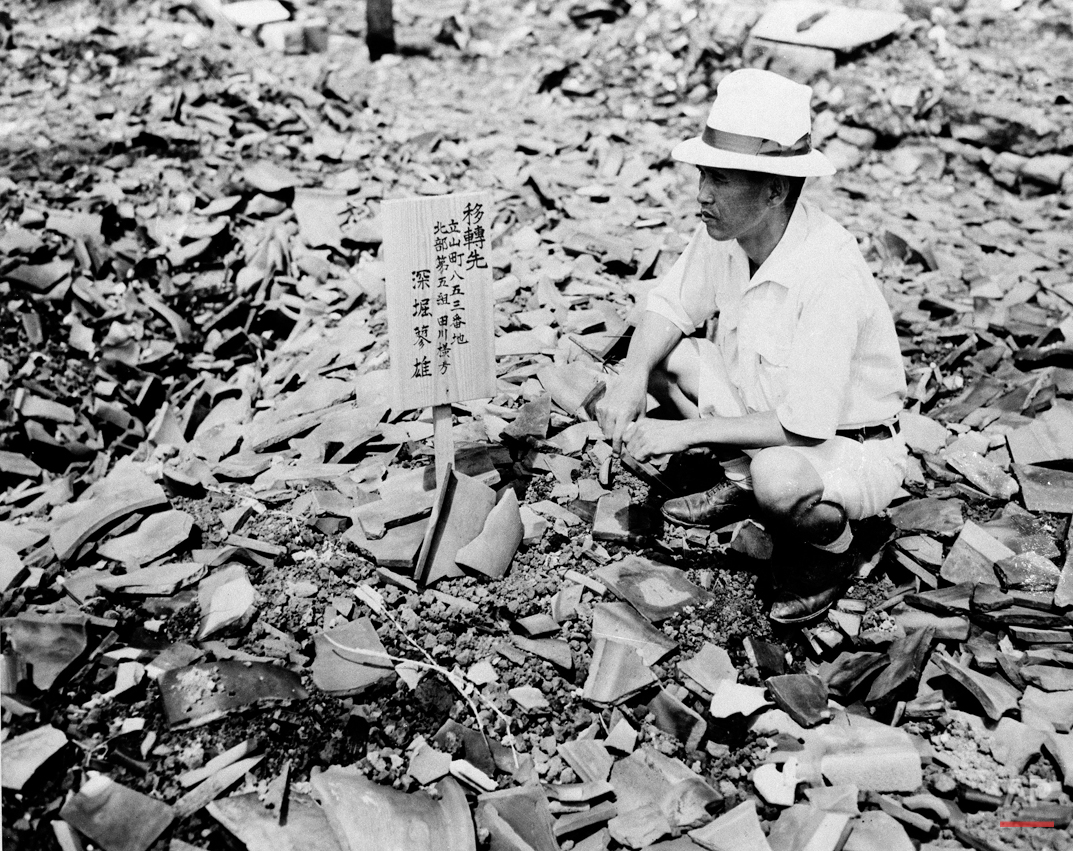 A civilian examines a sign in the middle of mass of rubble that once was a home in Nagasaki, Sept 14, 1945, one of the cities destroyed by atomic bomb.  (AP Photo)